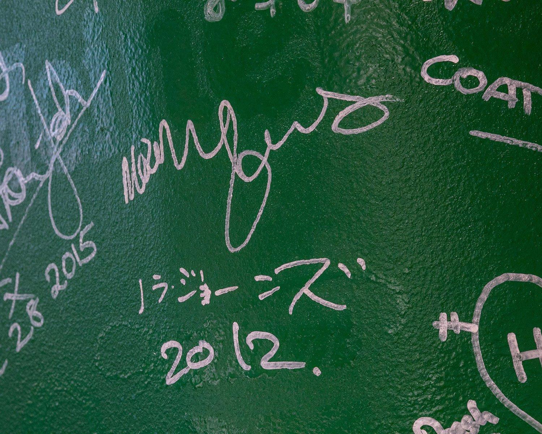 レジ横の柱に書かれた有名人のサイン(ノラ・ジョーンズの名前が)。