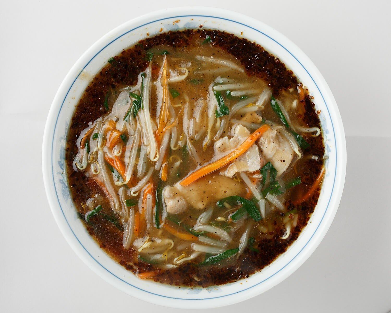 3種の油で炒めた焦がしネギが具のモヤシやニンジン、豚肉を囲む。麺は平打ちの卵麺。