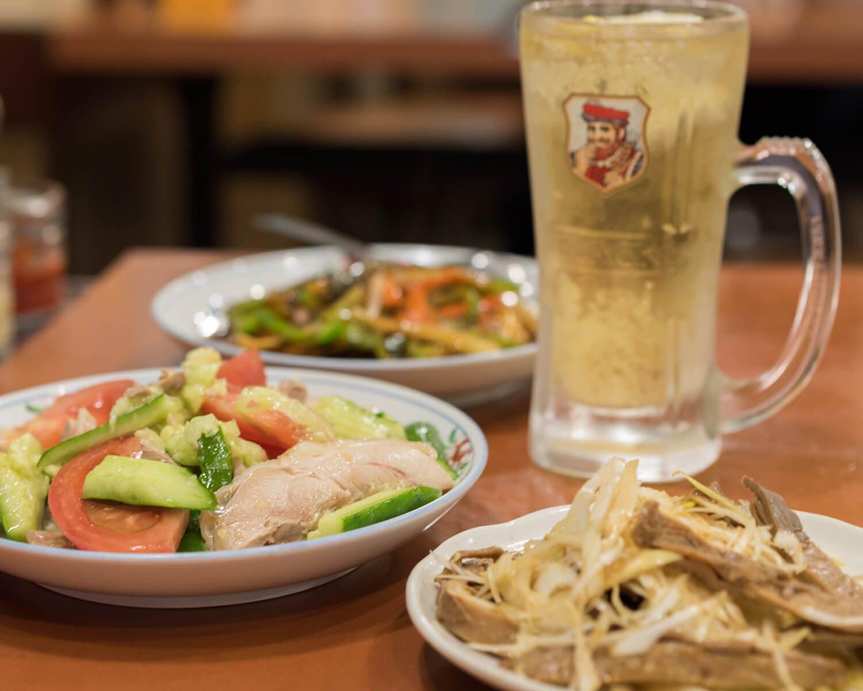 ガツとネギの和え300円(手前)など中華の枠を超えたつまみで昼から飲める。