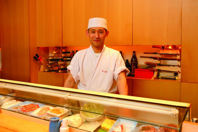 店主の加藤さん。長いカウンター席の奥で手際よく仕事をする。