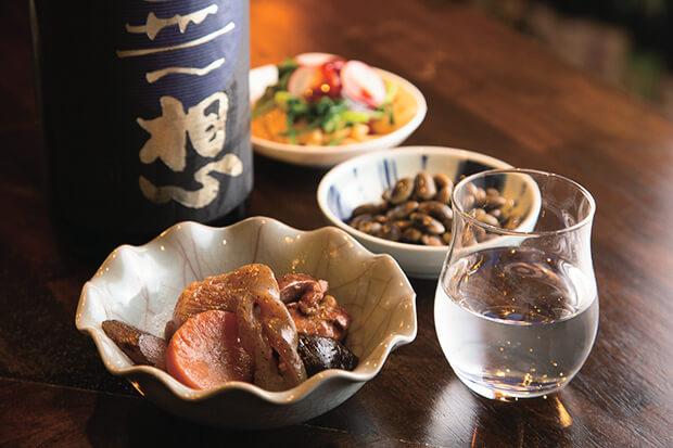 くらかけ豆の白たまり漬450円(中央)、香り爽やかな無想厳雪100㎖ 550円など。日本酒は約1週間で入れ替え。
