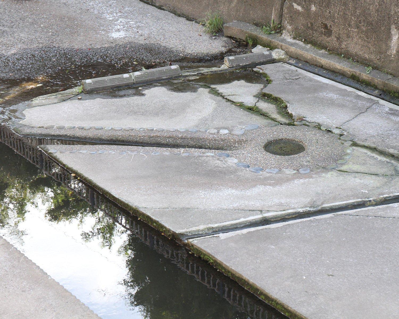 原寺分橋湧水。コンクリートの割れ目から、少し水が湧いているのが見えた。近くに湧水の仕組みを解説する看板も。
