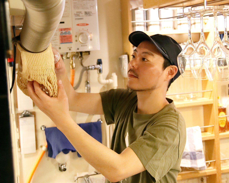2階からの注文はパイプにカプセルを落とす独特な方式。注文を受け取る中村さん。