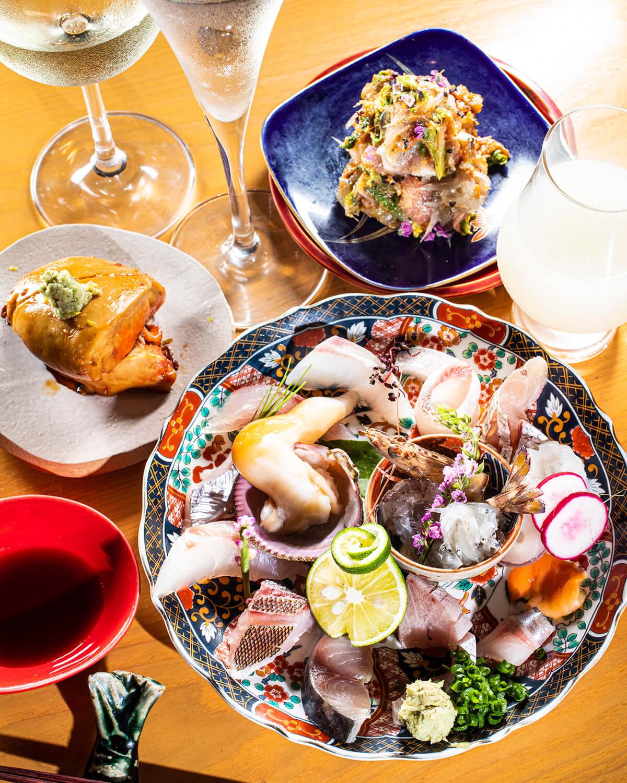 釣り魚を盛り付けた刺盛は1600円。赤酢あん肝680円(左)、海鮮とふきのとうのなめろう680円(奥)。日本酒は750円~。