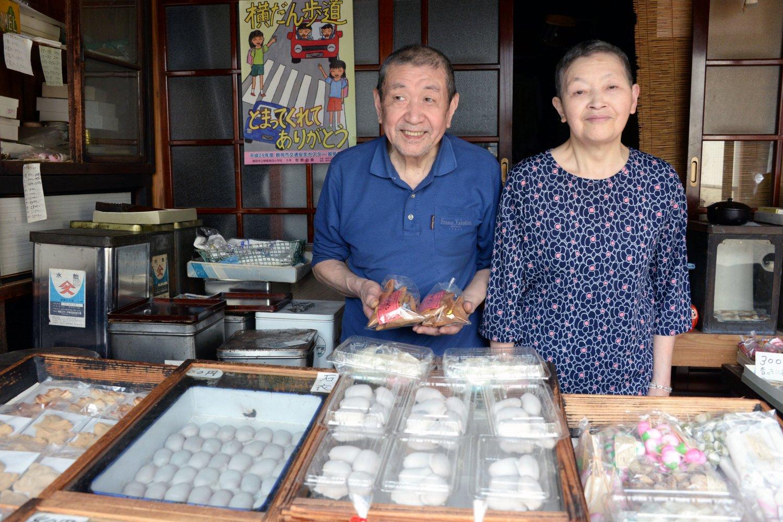 10代目の梅津善一さんご夫妻。店先の木枠ケースに駄菓子が並ぶ。