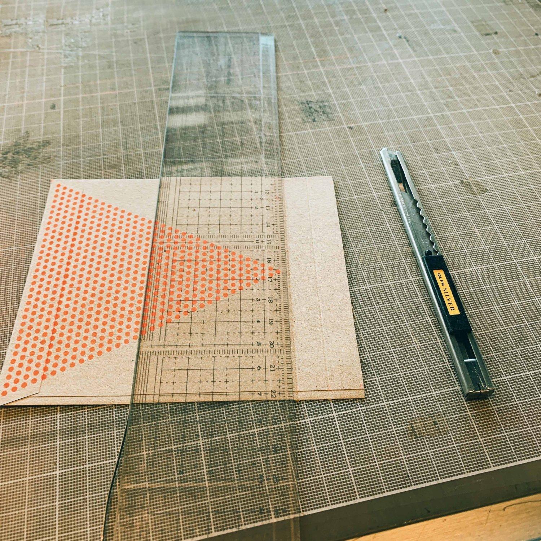 封筒上部をカットして、カッターで折り返し部分に折り目をつける作業。