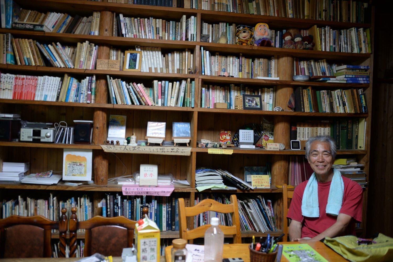 オーナーの長井三郎さん。フリースペースにぎっしりと本が並ぶ。