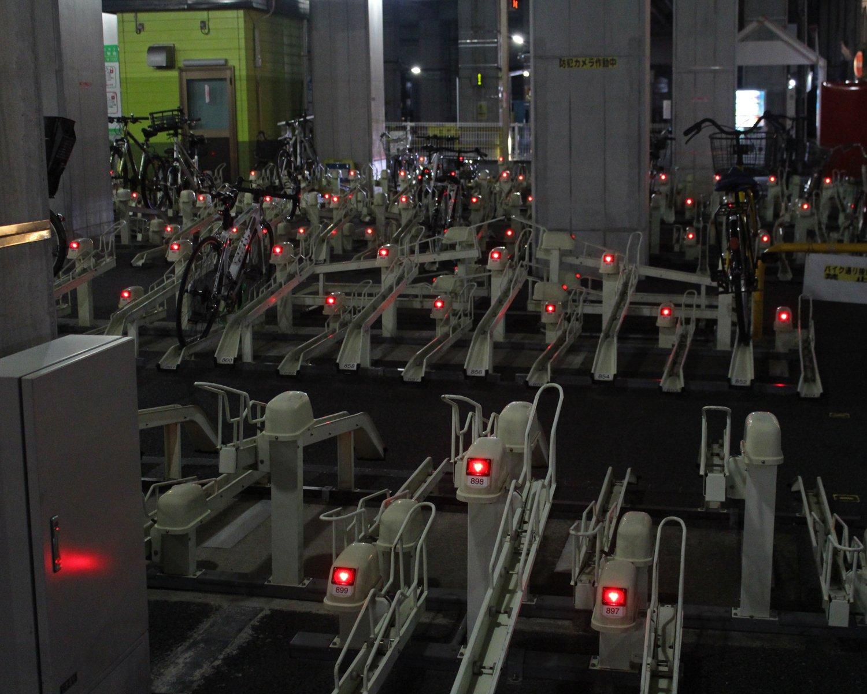 小田急線登戸駅の近くの高架下駐輪場。怒れる王蟲のようにたくさんの赤い目が光る。