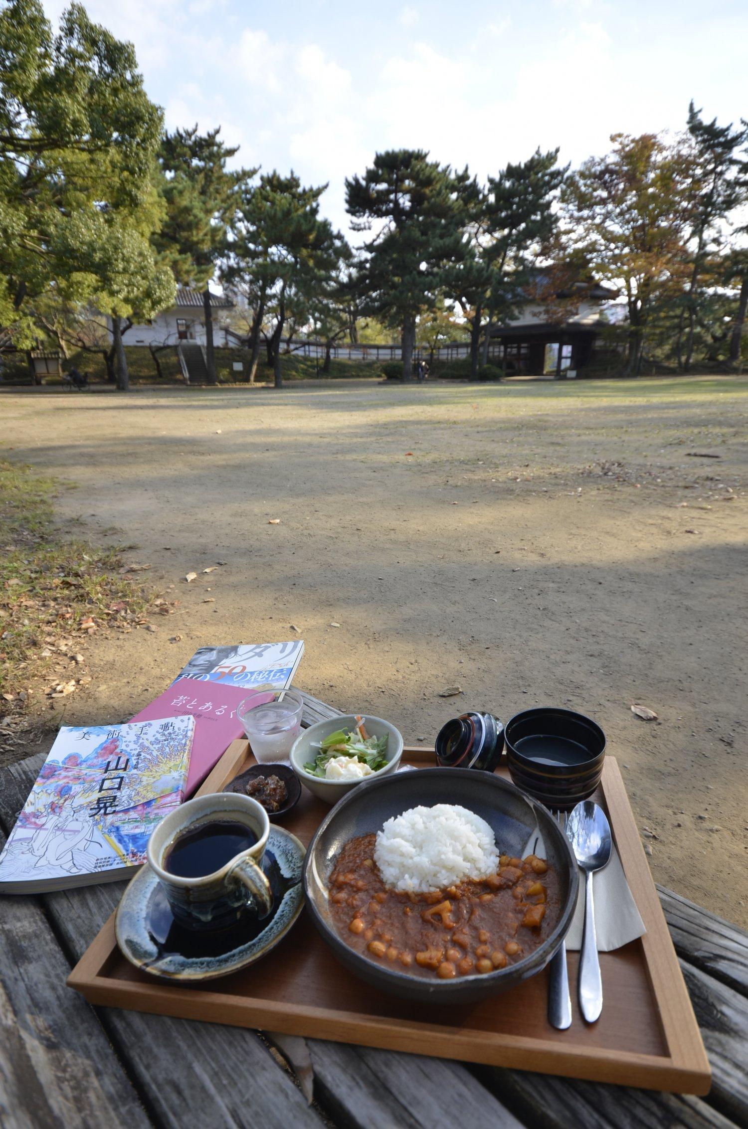 櫓(やぐら)門と櫓2棟に囲まれた本丸広場。テイクアウト可の城藤茶店のカレー850 円やコーヒー450 円、貸本(無料)でくつろごう。