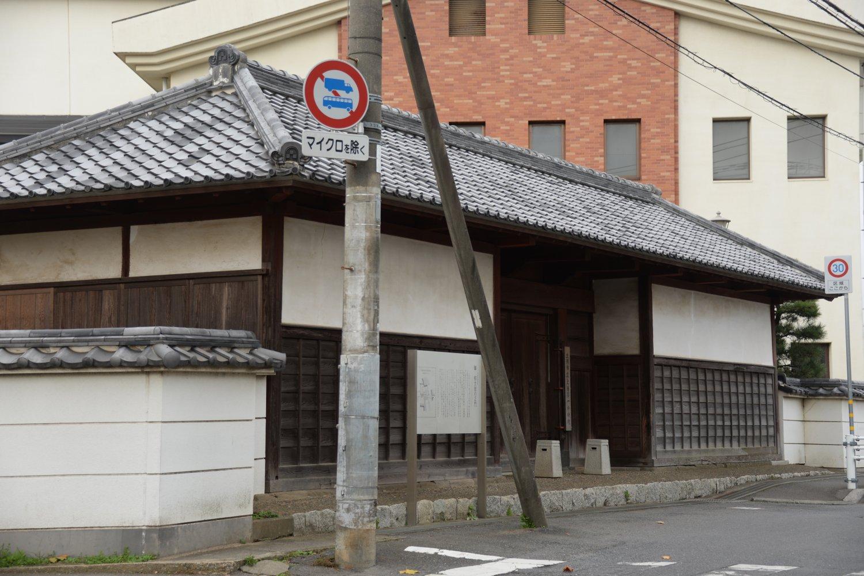 天保10 年(1839)築の正門が唯一の遺構。歩道橋から裏側も見られる。