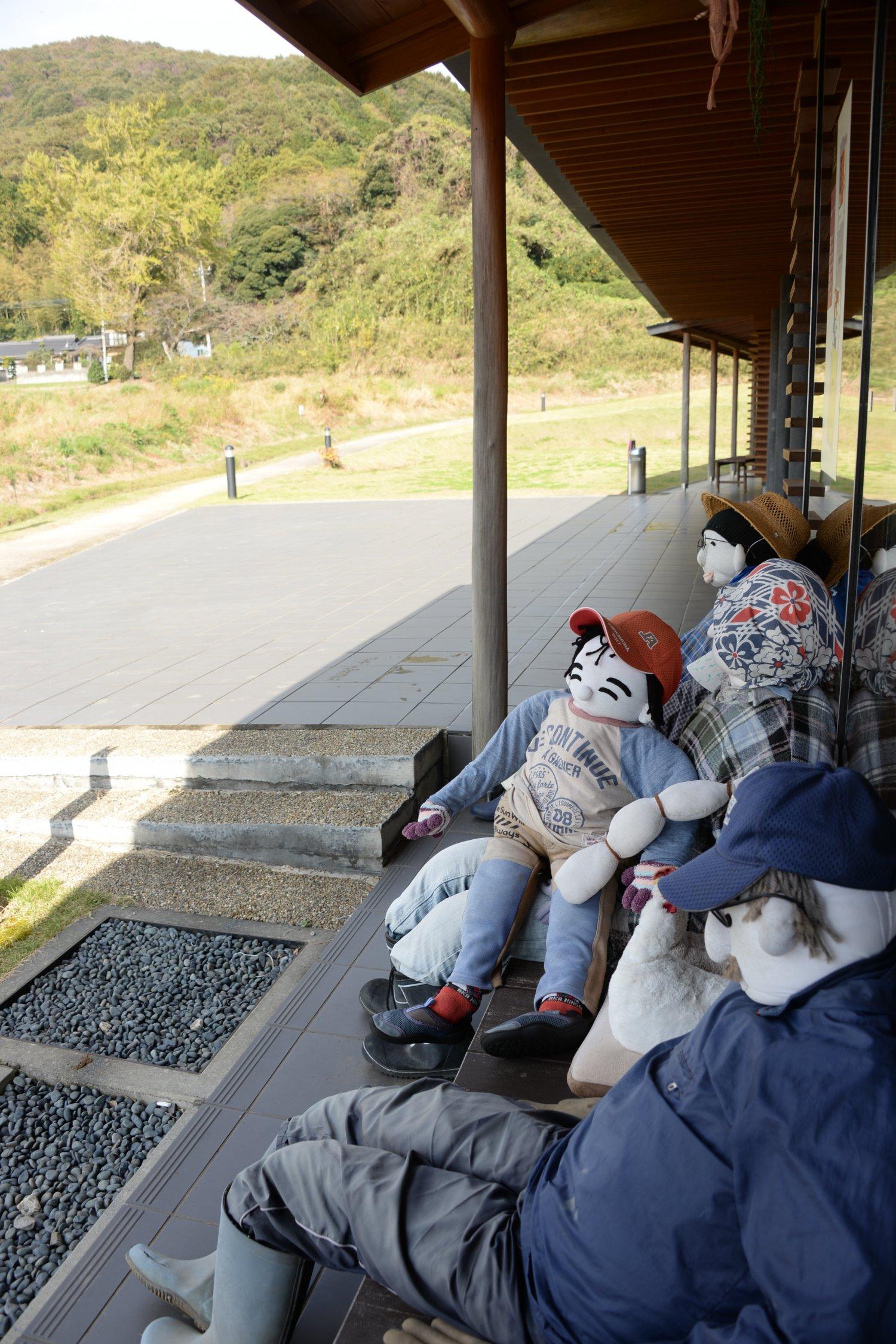 無料の休憩館は畳敷き。縁側に等身大の人形が小町山を向いて並ぶ。