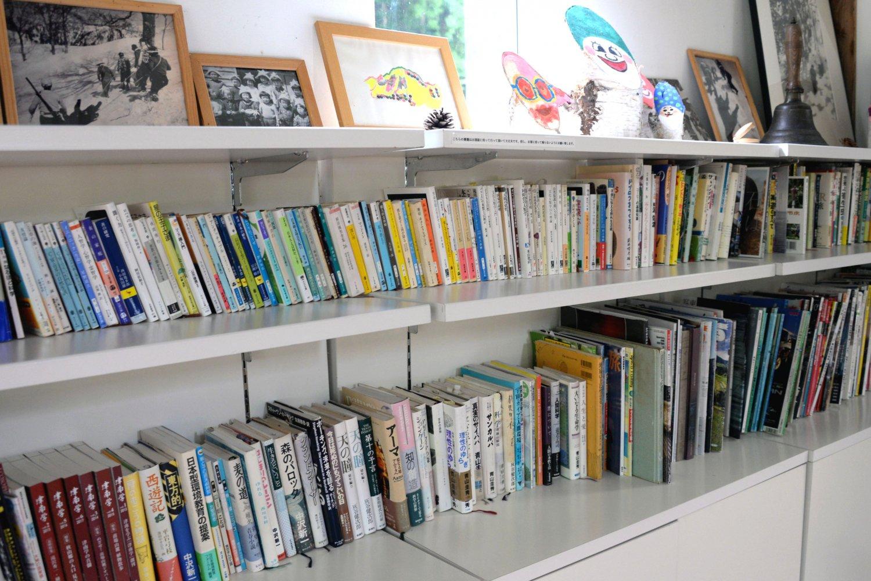 秋山郷や登山などの書籍が並ぶ本棚。学校で使われていたと思われる振り鐘も残る。