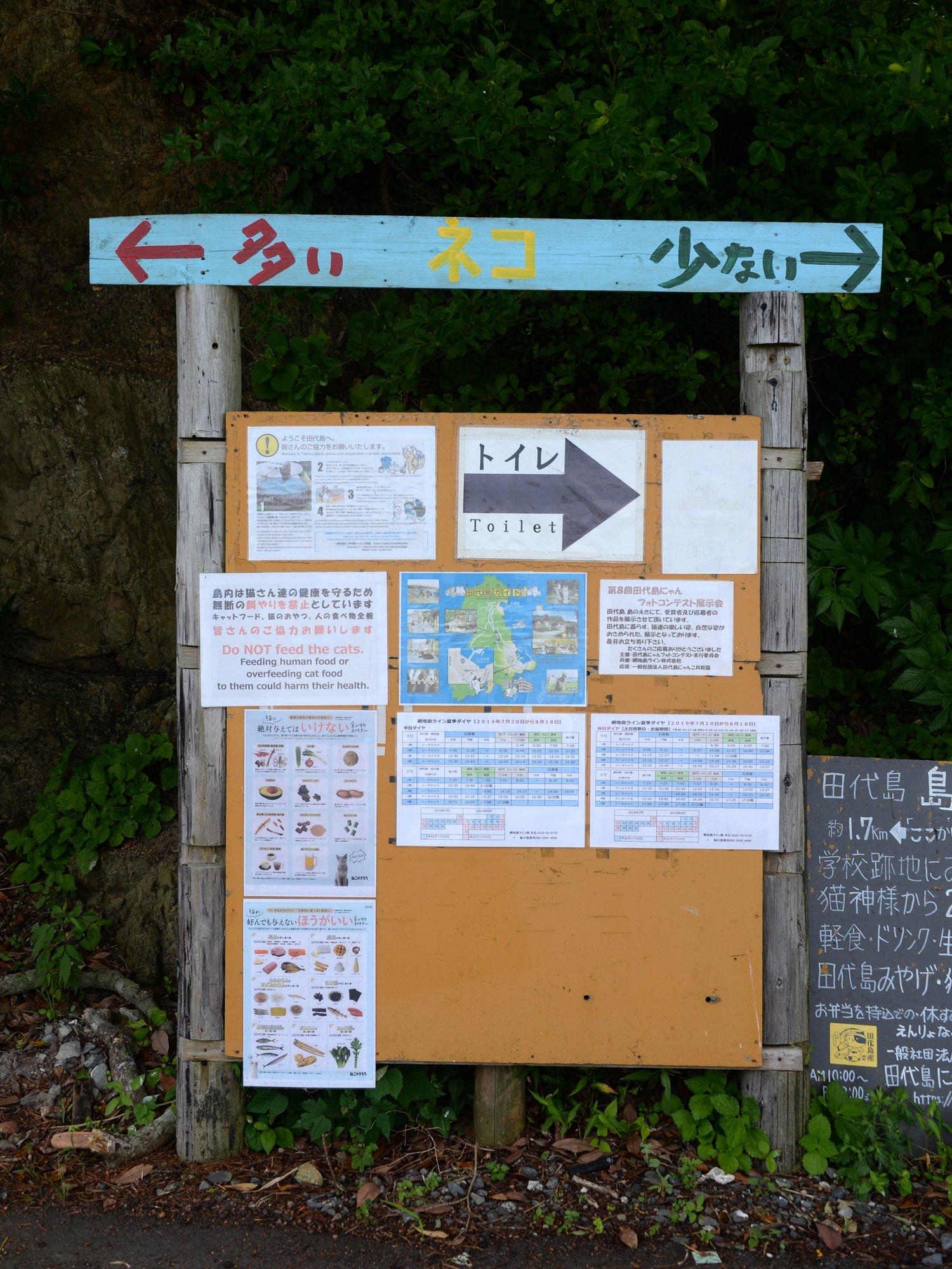仁斗田港そばの分岐に建つ道案内。 ネコの数情報で行先を示している。