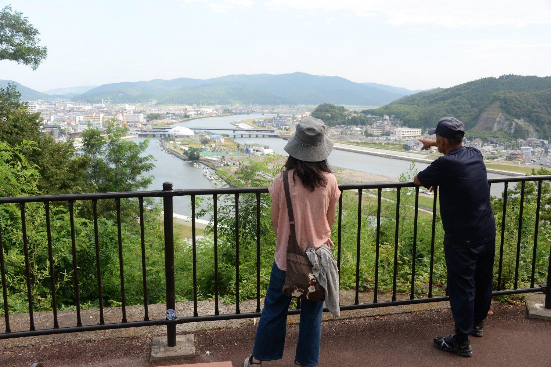 震災当時を語る散歩中の住民と、中州の「石ノ森萬画館」を眺める。