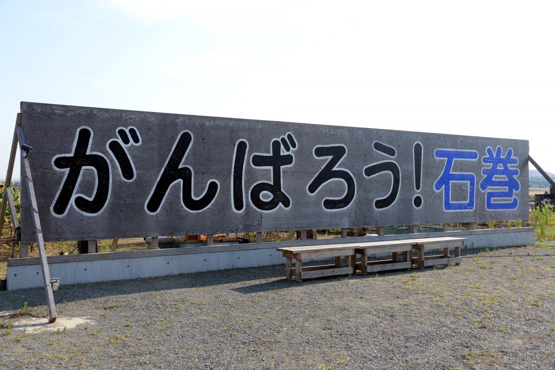 震災1ケ月後に建てられた看板のレプリカ。「石巻南浜津波復興祈念公園」(予定地)内にあり、そばに献花台も。