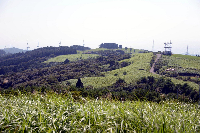 風力発電のプロペラが並び、牧草地が広がる上品山の山頂付近。