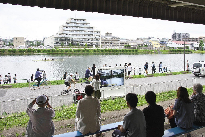 現在の戸田ボートコース。自転車や全速力の応援隊がボートと伴走し、右手の車が実況撮影して観客席のモニターに。