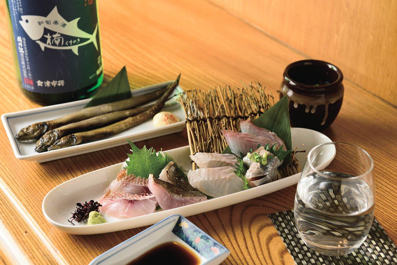 会津中将純米の楠ラベル550円。お刺身盛合せ一人前1210円、幻魚の一夜干し473円、そばの実がのった自家製冷奴275円。