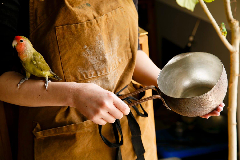 錫引きの銅製ミルクパン2万4750円。コザクラインコのむーちゃんも飛び入り参加。