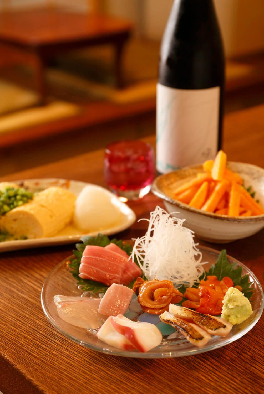 足立や浦和の市場から毎日仕入れる新鮮魚介の刺身盛合せや柿の山葵あえ(奥)などは、どれも地酒と相性よし。