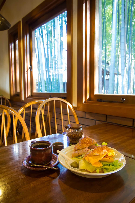 通常14時まで提供されているクロワッサンサンドセット1100円。ハムと卵の2種類でボリュームあり。独特な赤色のコーヒーカップは益子焼。額縁のような木の窓枠は内装で最もこだわった部分。
