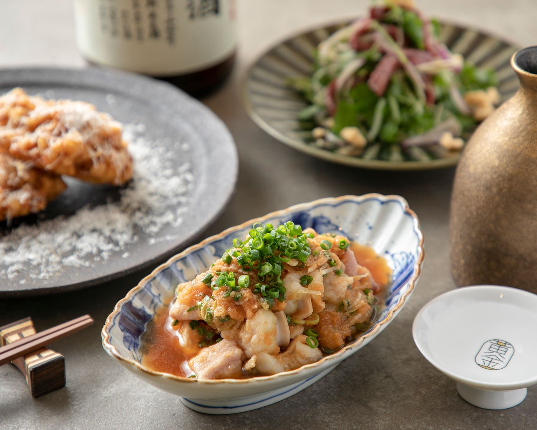 リードヴォーとトウモロコシのかき揚げ825円(左)など洋食出身の料理長が手掛ける牛モツ料理は絶品。日本酒グラス660円~。