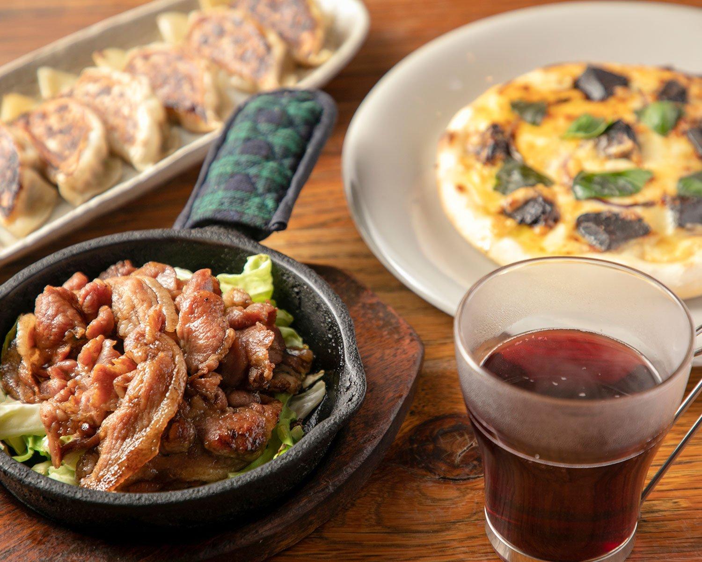 シナモン香るホットワイン650円、甘辛い豚肩ロースを鉄板で供するじゅうじゅう焼きLL1000円(左)。