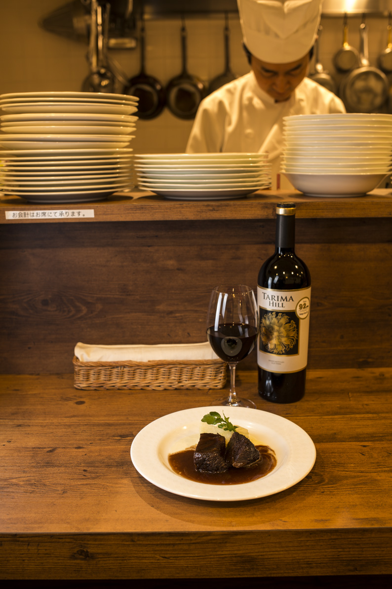 牛ほほ肉の赤ワイン煮ハーフサイズ1000円はスペインワインTARIMA HILLグラス850円と相性よし。