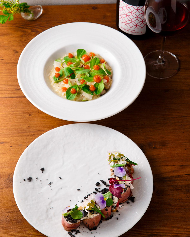 鴨肉の冷製仕立て(下)とオレンジジュレの彩りが美しいそら豆とサルシッチャのリゾット。華やかな料理にワインが進む。ワインは200種以上。(料理はイメージ画像)