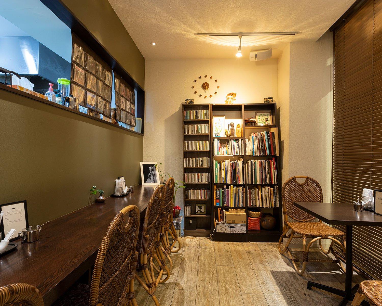 ゆったりした店内には書籍や民芸品が。新介さんの描い た絵画も飾られている。