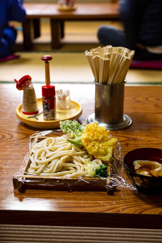 もりうどん500円と肉汁50円、玉ねぎと春菊の天ぷら各70円。食べきれないときは、持ち帰りできるよう麺の下にはラップ。