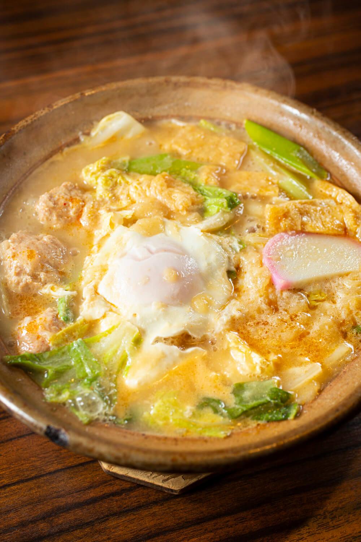 特製旨辛つくねの辛味、白菜の甘み、天かすのコクなどがつゆに溶け、後ひく旨さ。有田焼の鍋は最後まで熱々。