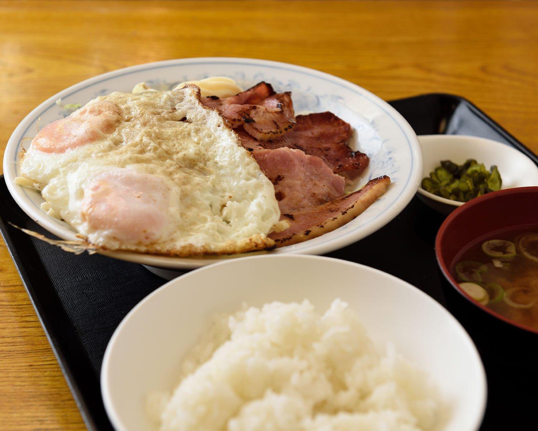 コショウたっぷりスパイシーなベーコンエッグ定食950円。目玉焼きの下にスパサラ。