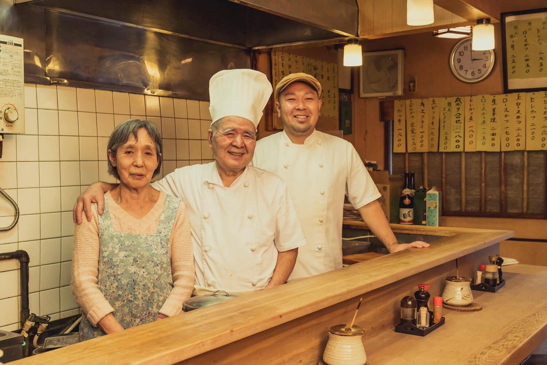 「しょうが焼きを食べると元気になる」と和子さん。初代節男さん(中央)、2代目隆さん。親子3人でのれんを守る。