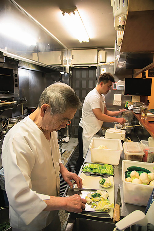 アキラさん(奥)と義父・憲昭さん。サバの味噌煮は憲昭さんが担当する。