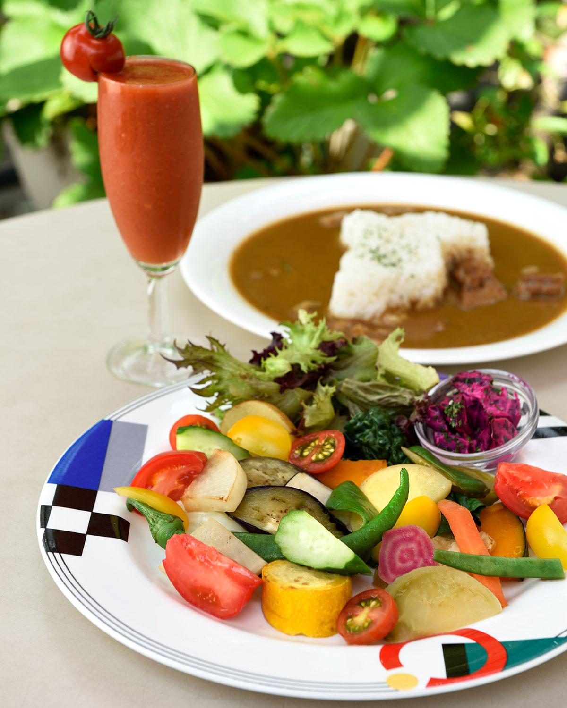 グリルした野菜や サラダが盛られた皿が付くいしい 農園カレー1100円、一平トマトのトマトジュース693円(季節限定)。