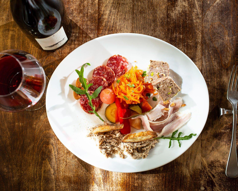 ワインを愉しむお肉屋さんの盛合せ2090円× 軽い赤。ワインはグラス880円~、ボトルは200種以上から選べる。