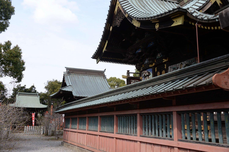 華麗な彫刻が施された本殿周り。左奥に八幡宮稲荷神社が見える。