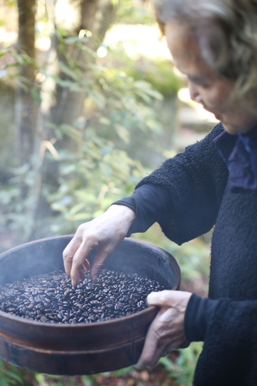 コーヒー豆は、骨董品のような焙煎機で煎る。焦げた豆を撥(は)ねる内田さん。「庭の土に還してあげるのよ」。