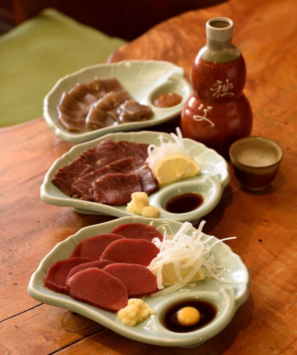 下から馬刺し1500円、鹿刺し1500円、刺身こんにゃく700円。日本酒は秩父錦本醸造が3合1600円。
