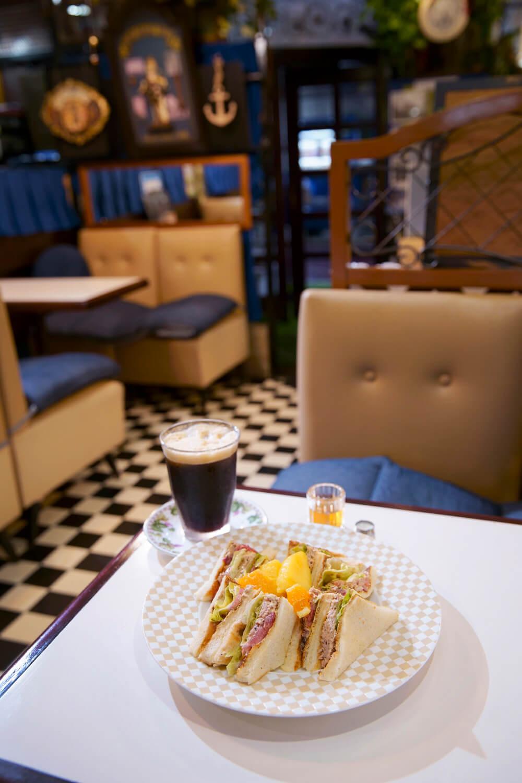 野菜とツナのサンド1190 円はブレンドか紅茶付き。泡でふたをしたレギュラーアイスコーヒーは+200円。