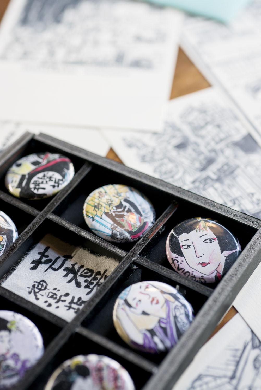 神楽坂の 風景を描いたカード(オリジナル封筒入り7枚セットで700円)やバッジ(1個350円)。