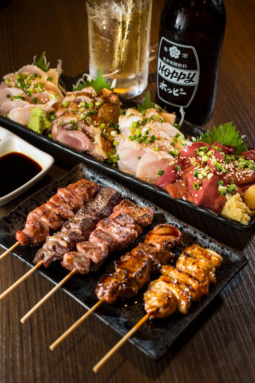手前からシロ、レバー、ハツなど豚の串焼きは全150円。鳥刺し四点盛り1980円、ホッピー450円。(全て税抜き)
