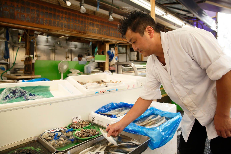 『魚次三』で魚を物色する料理長。