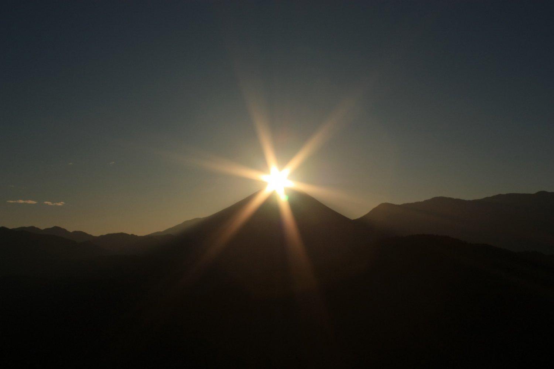 富士山の山頂と昇る朝日が重なる幻想的な光景。