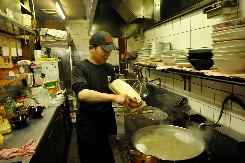 厨房に立つ店長の張さん。華麗に刀削麺を作る。