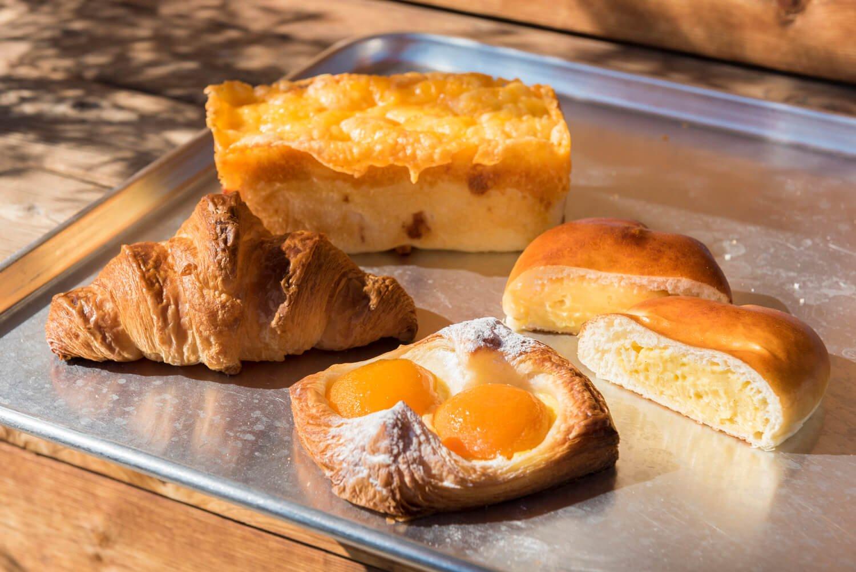 チーズチーズチーズ!!450円(奥)、クリームたっぷりクリームパン140円(右)、クロワッサン150円(左)、アプリコットのデニッシュ(期間限定製品)250円(手前)。