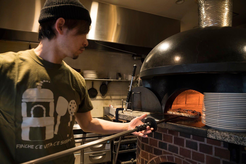 薪窯の火力を見ながら、ナポリピッツァを1分で焼き上げる。