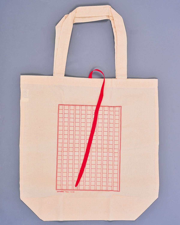 アトリエショップ限定の原稿用紙柄のオリジナルエコバッグ。しおりを模した紐でくるっとまるめてしまえる。原稿用紙に何か書き込んでカスタマイズしてもよし。990円。