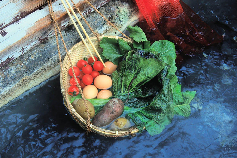 湧き出る90度の熱湯で卵や野菜を自由に茹でられる川沿いの湯筒。